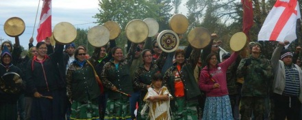 Women raise their drums on Mi'kmaq territory in Rexton, NB. Photo featured by Dallas MacQuarrie at NB Media Co-Op.
