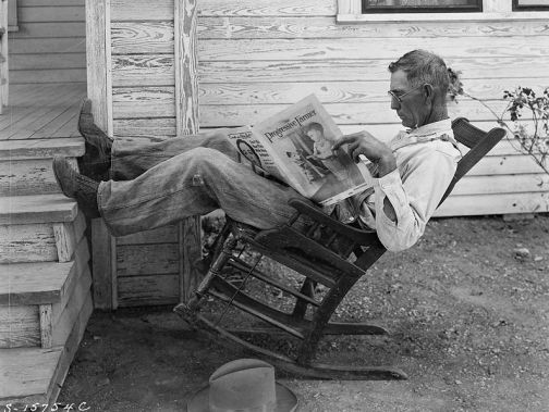 Farmer reading his farm paper_George Ackerman